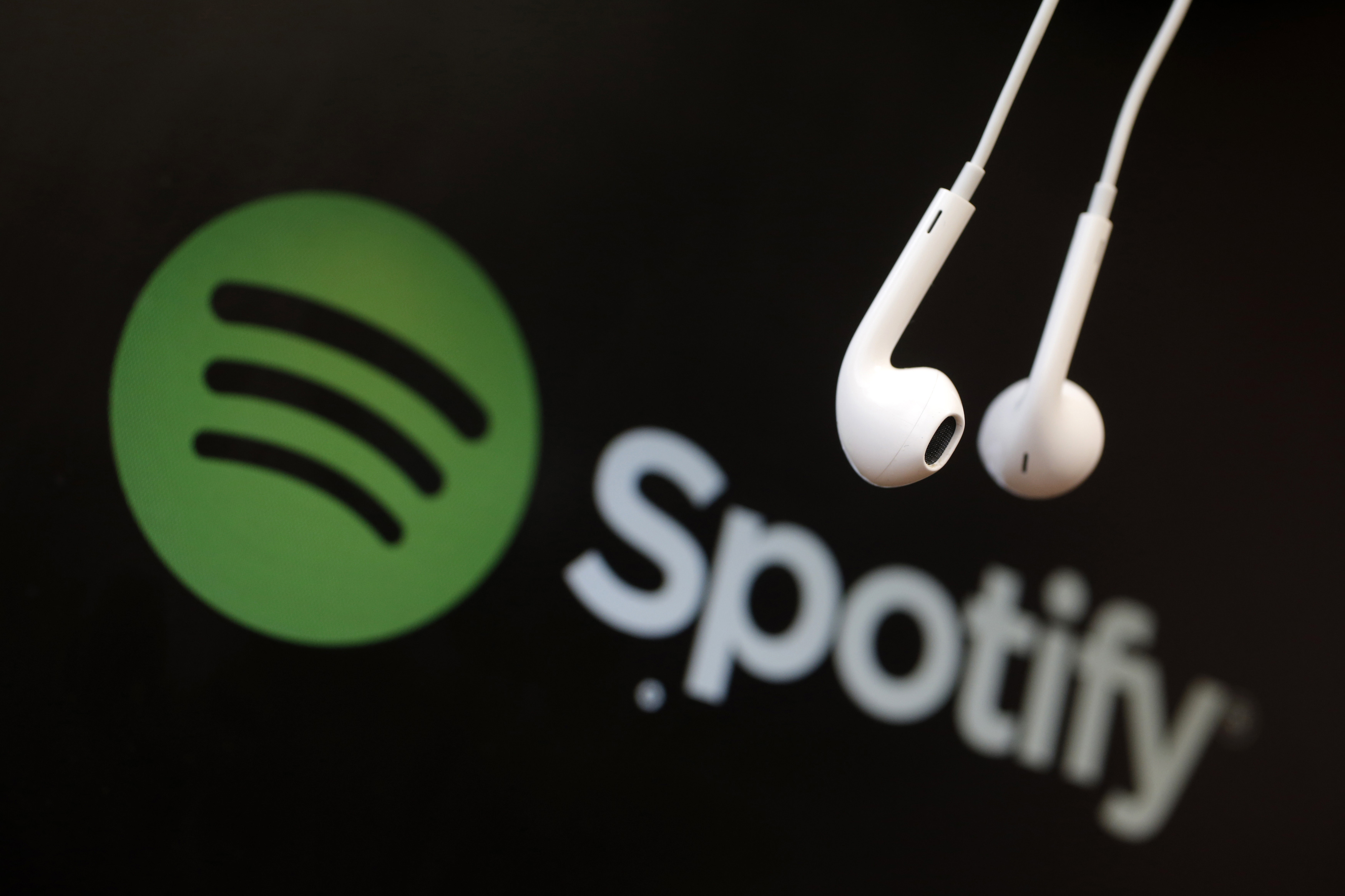 Headphones are seen in front of a logo of online music streaming service Spotify in this illustration picture taken in Strasbourg, February 18, 2014. Spotify is recruiting a U.S. financial reporting specialist, adding to speculation that the Swedish start-up is preparing for a share listing, which one banker said could value the firm at as much as $8 billion. REUTERS/Christian Hartmann (FRANCE - Tags: BUSINESS ENTERTAINMENT LOGO) - RTX1914U